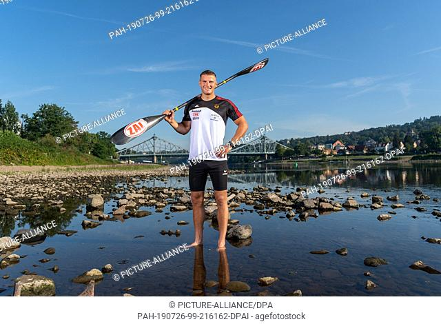"""25 July 2019, Saxony, Dresden: Tom Liebscher, Olympic Canoe Champion, is standing in front of the """"""""Blue Wonder Bridge"""""""" after a training session for the World..."""
