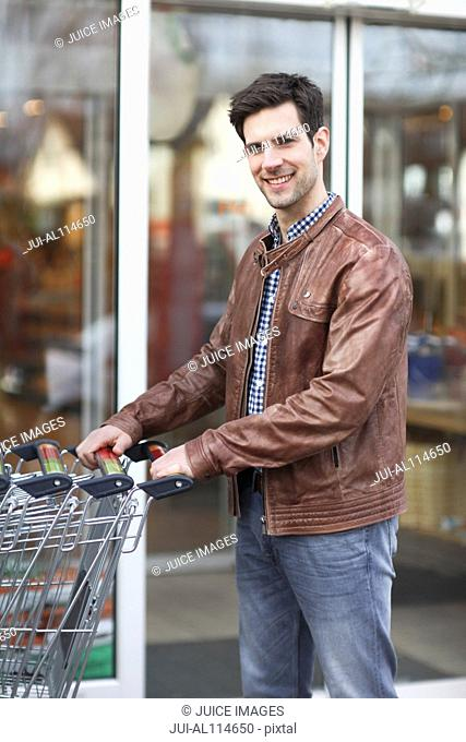 Portrait of mid adult man with supermarket trolley