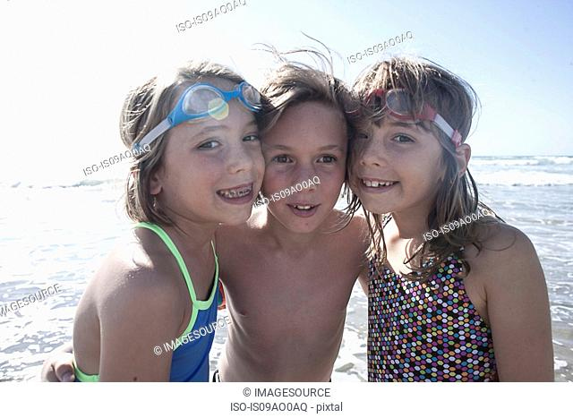 Portrait of twin sisters and brother on beach, Del Mar, California, USA