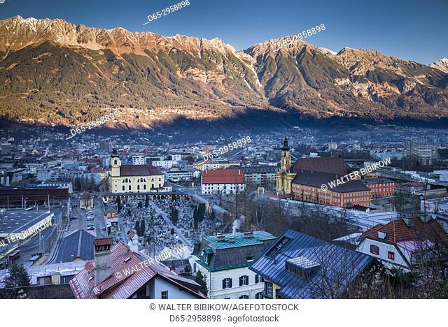 Austria, Tyrol, Innsbruck, elevated city view with the Wilten Basilica and Wilten Abbey Church, dawn, winter