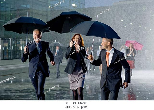 Businesspeople walking past a modern office building holding umbrellas in heavy rain