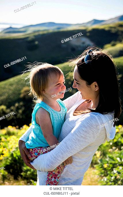Mother holding young daughter, hiking the Bonneville Shoreline Trail in the Wasatch Foothills above Salt Lake City, Utah, USA