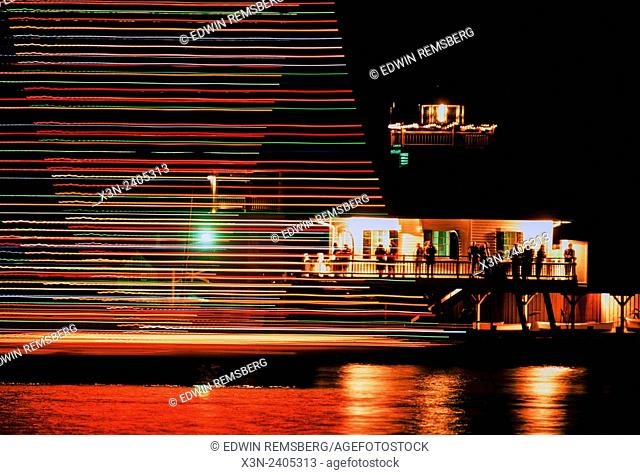 Christmas in St. MIchaels: Parade of lighted boats pass the Hooper Strait Lighthouse in St. Michaels Harbor
