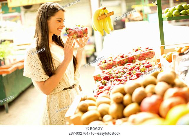 Young woman looking and buying fresh fruit at the market