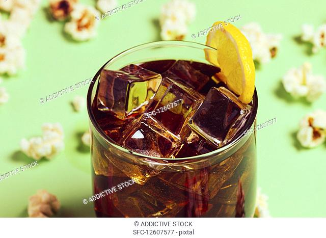 Popcorn on table near drink in glass with ice and lemon