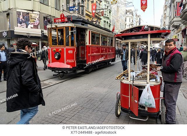 Tram and chestnut vendor in Istiklal Caddesi, one of Istanbuls main shopping centres. Beyoglu, Istanbul, Turkey,