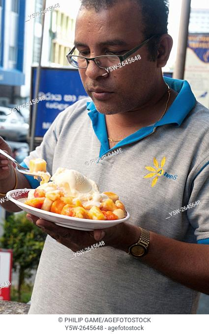 Sri Lankan man enjoying fresh fruit with ice-cream, Colombo