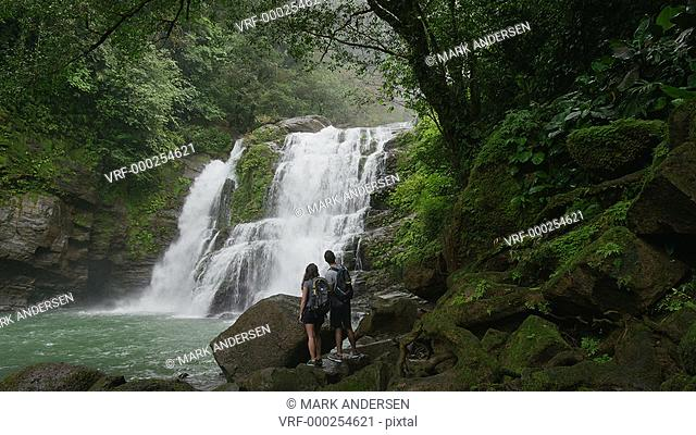 Wide slow motion zoom in of couple admiring waterfall in rain forest / Santa Juana, , Costa Rica