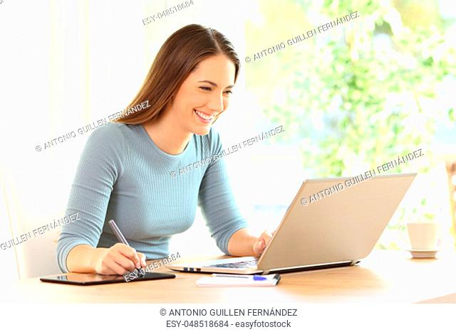Happy woman drawing with a display pen and a laptop on a desk at home