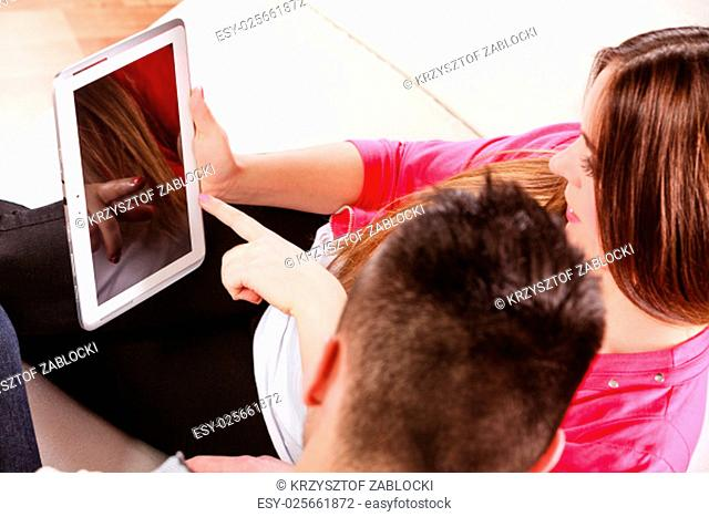 modern technologies and relationships leisure concept. young couple using tablet pc computer sitting on couch at home websurfing on internet,high angle view