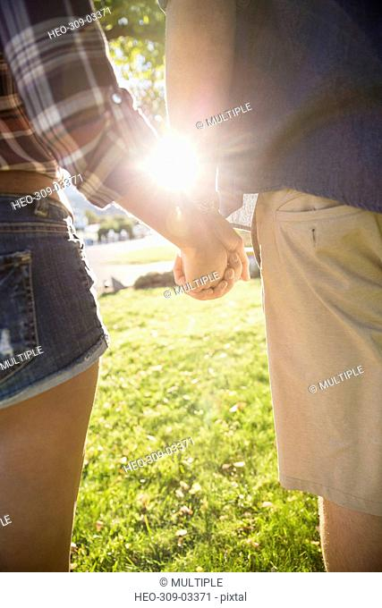Close up young couple holding hands in sunny summer yard