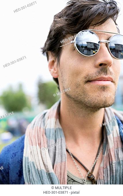 Close up young brunette man wearing sunglasses looking away