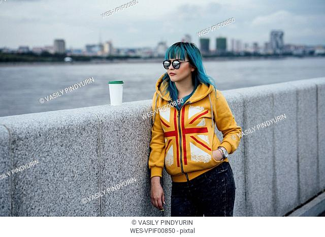 Portrait of young woman with dyed blue hair wearing fashionable hooded jacket looking at distance