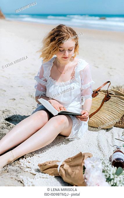 Young woman reading book on beach, Menemsha, Martha's Vineyard, Massachusetts, USA