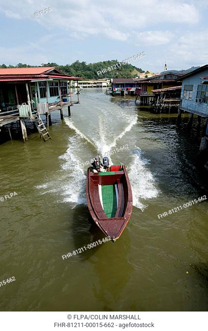 Water taxi speedboat passing shacks on stilts in river, Water Village (Kampong Ayer), Brunei River, Bandar Seri Begawan, Brunei, March