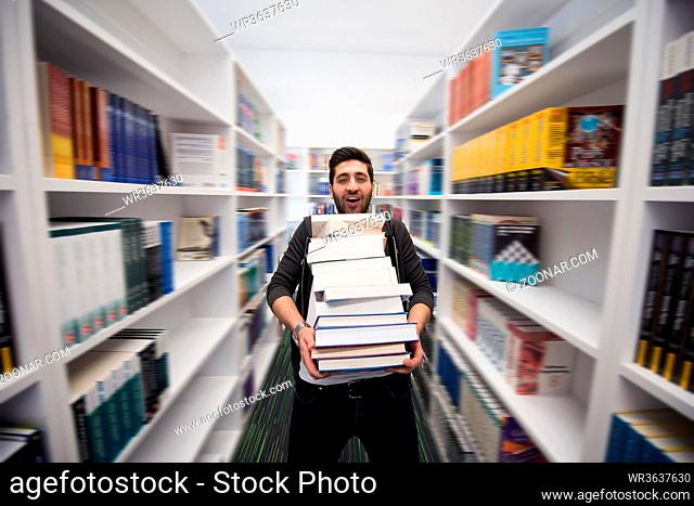 Student holding lot of books in school library. Hard worker and persistence concept