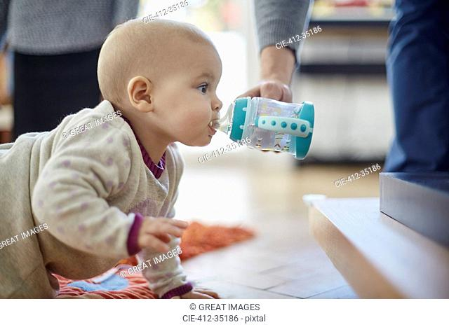 Baby girl crawling and drinking from sip cup