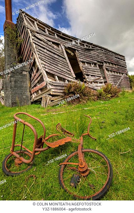 Rusty child's tricycle in front of derelict shed, Kumara, West Coast, New Zealand