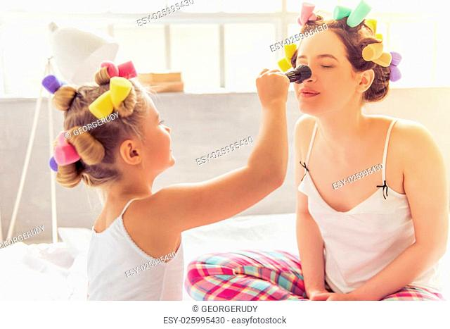 Beautiful young mother and her daughter in pajamas and with hair curlers are doing makeup, talking and laughing, sitting on bed at home