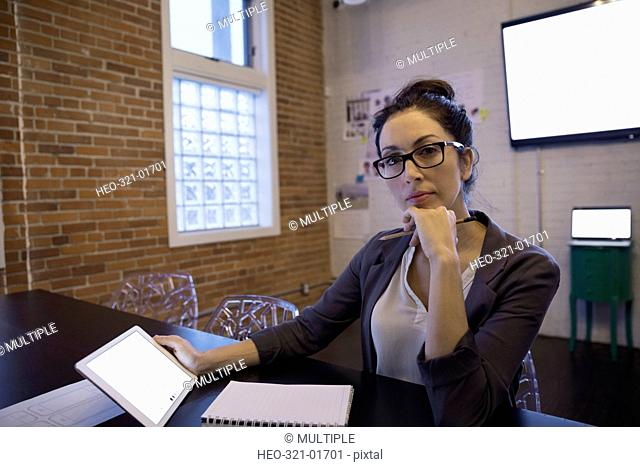 Portrait confident businesswoman using digital tablet at conference room table