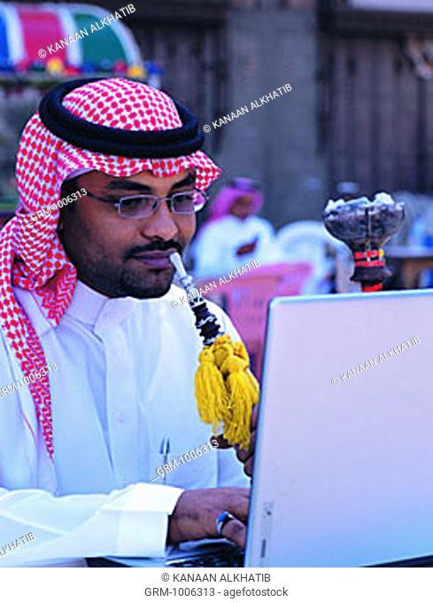 Saudi man working on laptop and smoking shisha in Old Town of Jeddah, Saudi Arabia