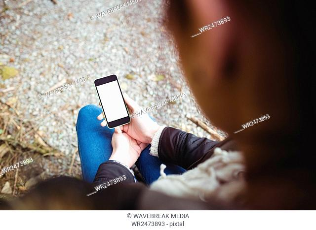 high angle view of woman watching her smartphone
