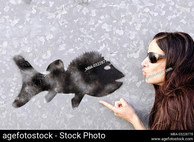 Woman kisses black graffiti fish on a gray wall