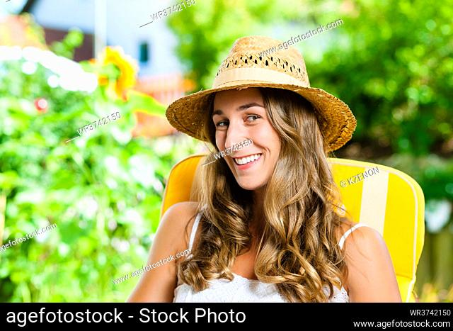 Woman tanning herself in the sun on a lounge chair and enjoying the free time in her garden