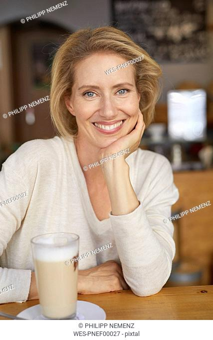 Portrait of relaxed woman with Latte Macchiato in a coffee shop
