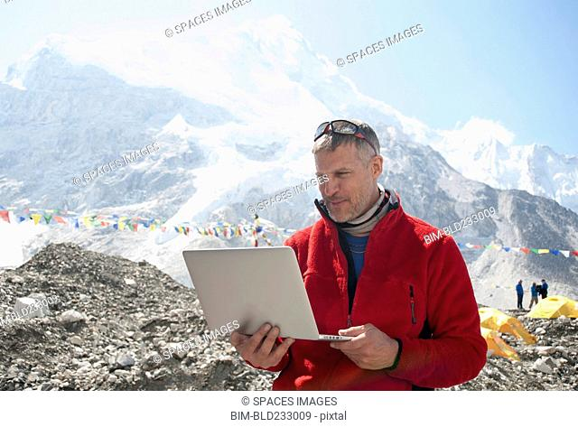 Man using laptop on snowy mountain