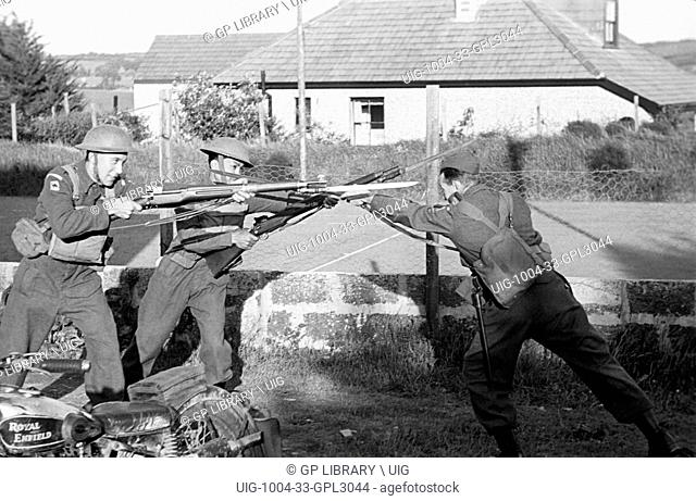 Three men in armed forces uniforms training how best to use a fixed bayonet in close quarters combat in war time Britain