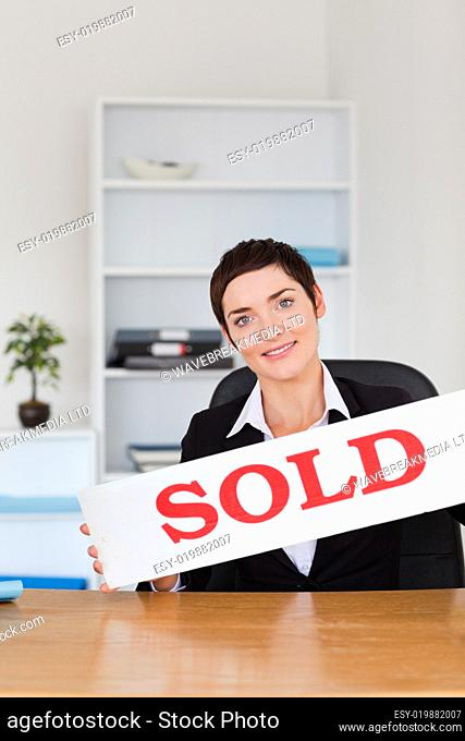 Portrait of a real estate agent with a sold panel