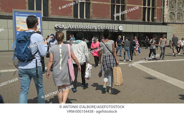 People walking in the square outside the railways Centraal Station. Amsterdam. Netherland