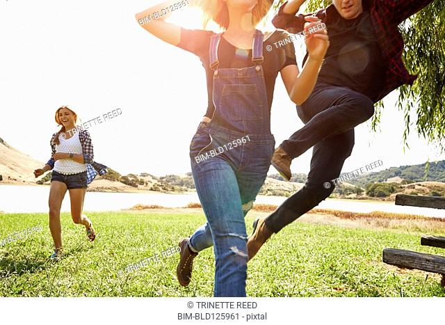 Friends running and jumping in park