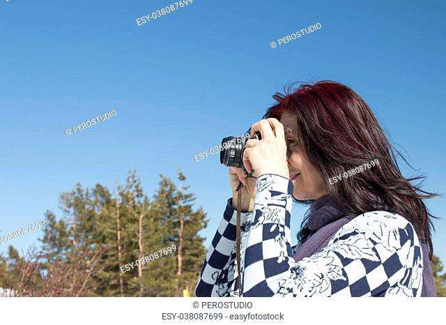 Redhead woman with an old camera in winter against blue sky