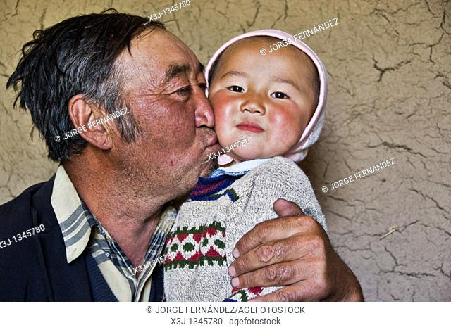 Old man with grandson at home  Kyrgyzstan
