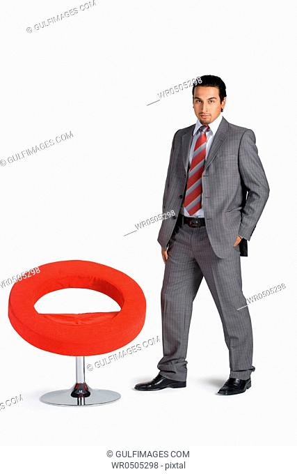 Young businessman standing by swivel chair, portrait