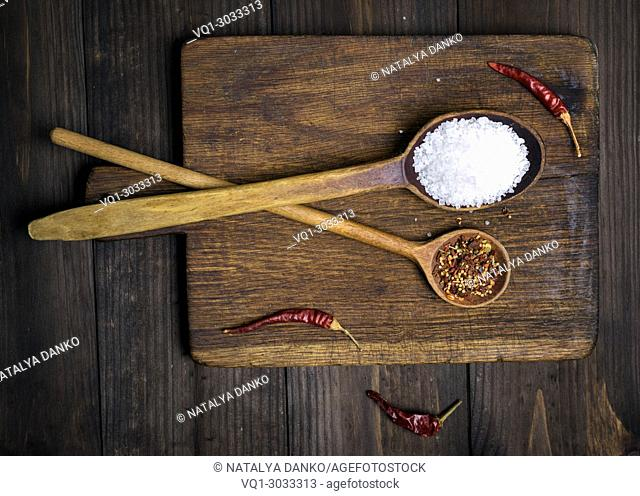 wooden spoon with white salt and spices on a cutting board, top view