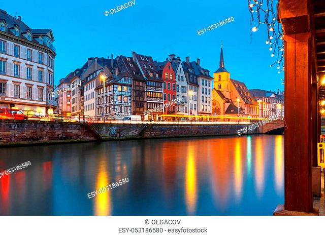 Picturesque quay and church of Saint Nicolas with mirror reflections in the river Ile and Christmas garland during evening blue hour, Strasbourg, Alsace, France
