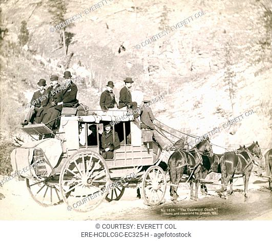 The Deadwood Coach. Side view of a stagecoach, formally dressed men sitting in and on top of coach. Deadwood, SD. John C. Grabill, 1889