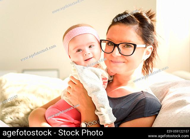Mother holding beautiful baby girl in bright sunny room. Motherhood background