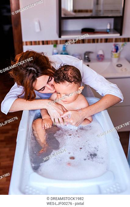 Mother bathing her little son