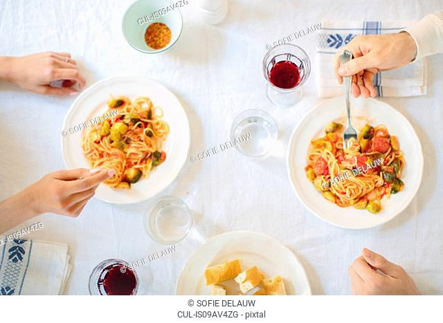 Overhead view of couples hands eating spaghetti at table