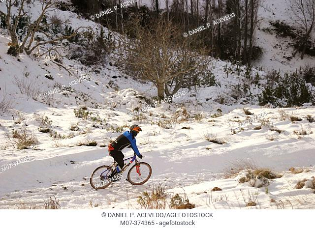 Man mountain biking on snow