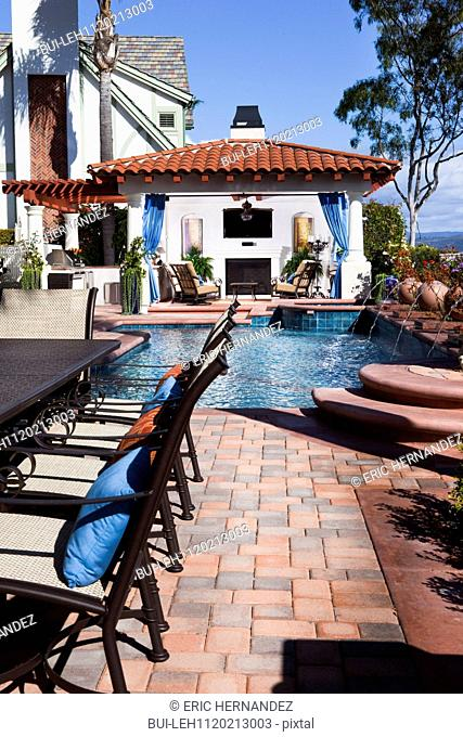Chairs at cropped table with swimming pool in the background; Laguna Niguel; California; USA
