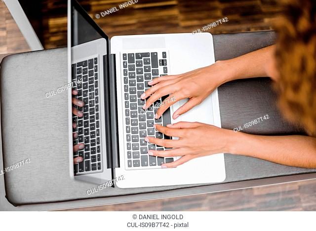 Overhead view of young woman typing on laptop