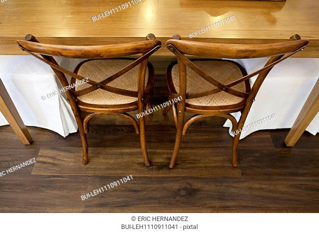High angle view of wooden chairs at cropped dining table at home