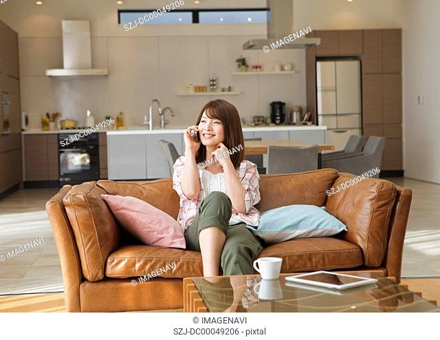 Middle-aged woman talking on a phone on a sofa