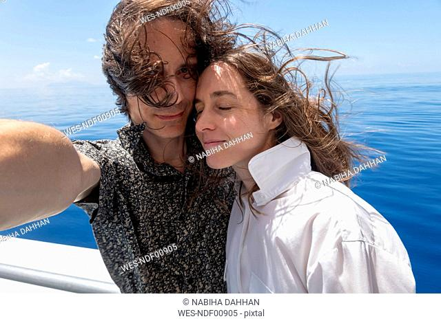 Seychelles, Indian Ocean, mature couple taking selfie on ferry