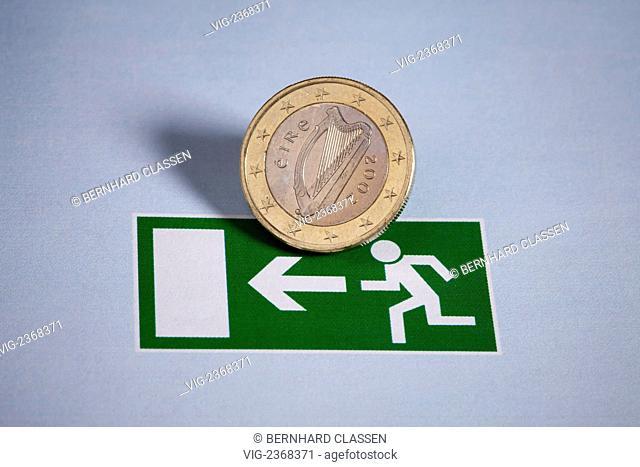 GERMANY, LUENEBURG, 24.01.2011, Irish 1 Euro coin on an emergency exit sign. - Lueneburg, Germany, 24/01/2011